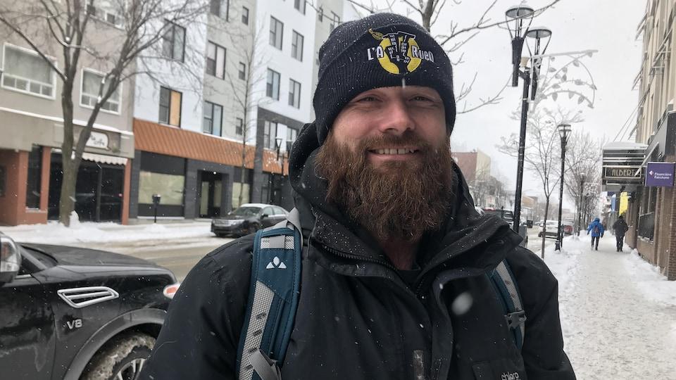 Un homme à la longue barbe, portant un sac à dos, sourit au centre-ville de Rouyn-Noranda.