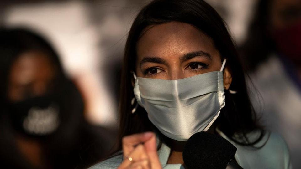 Alexandria Ocasio-Cortez parle dans un micro, entourée de personnes. Elle porte un couvre-visage.