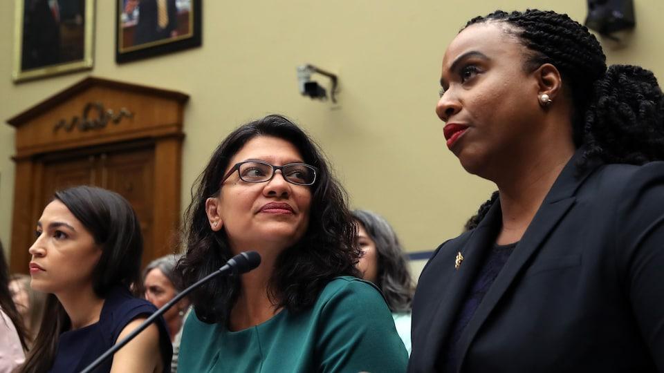 Trois femmes assises côte à côte écoutent un témoignage.