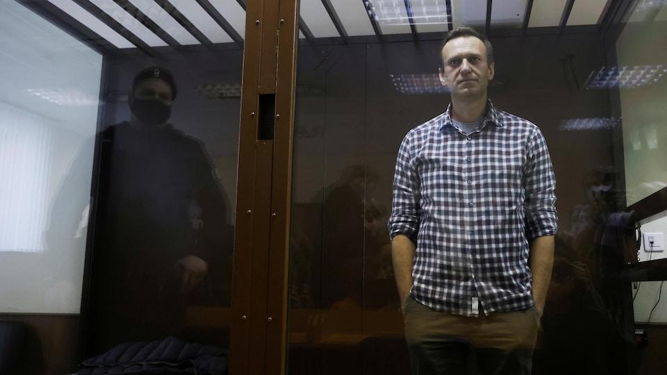 Alexeï Navalny est debout derrière une porte vitrée.