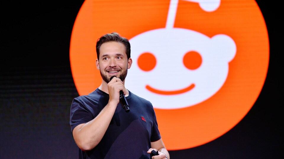 Un homme parle dans un micro devant le logo du réseau social Reddit.