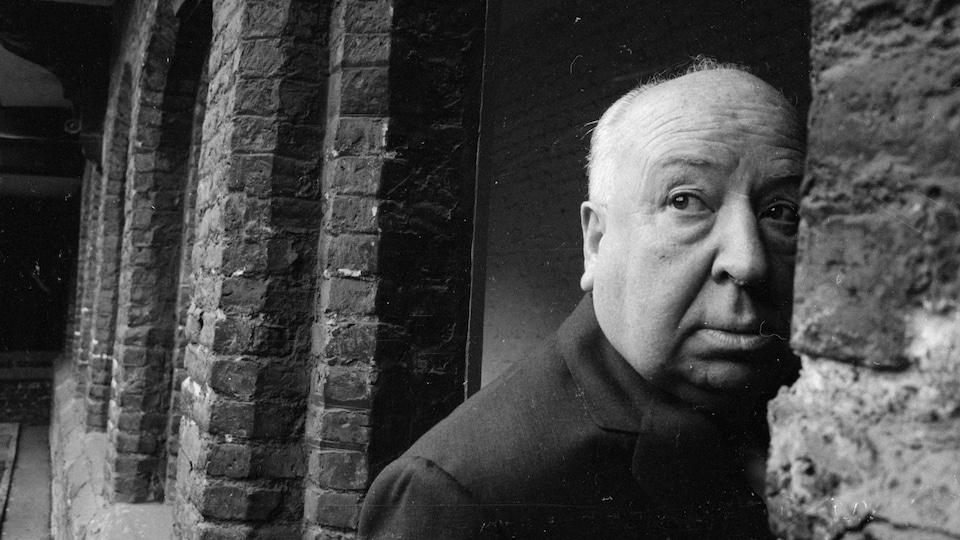 Alfred Hitchcock regarde sur le côté, alors qu'il fait face à un mur en pierre.