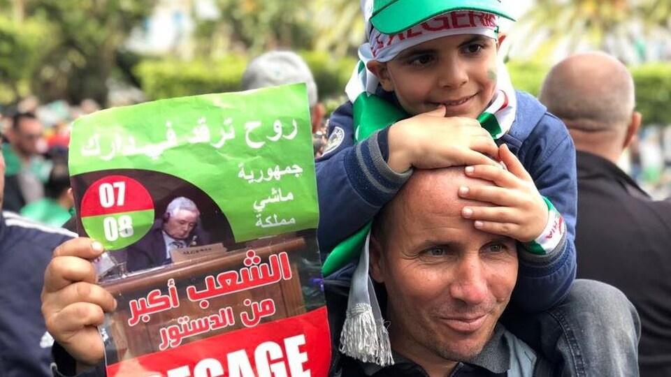 Un homme dans une manifestation à Alger brandit une affichette où l'on peut lire «Dégage».