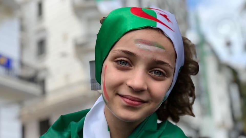 Une fillette participe aux manifestations à Alger, le drapeau en guise de coiffe.