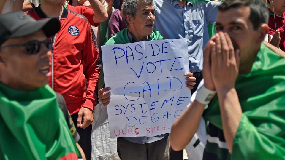 « Pas de vote Gaïd système dégage », peut-on lire sur une pancarte que tient un manifestant.