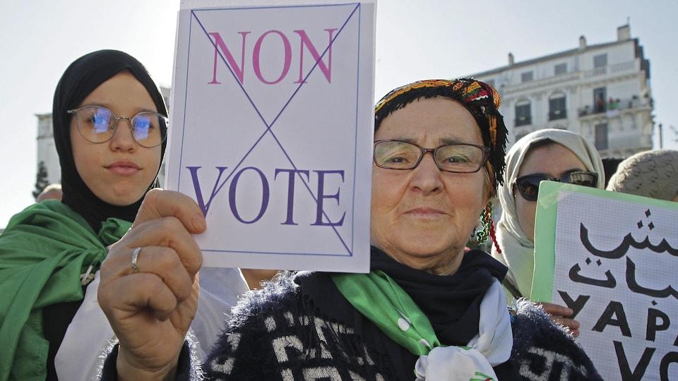 Une manifestante algérienne brandit une pancarte sur laquelle il est écrit « Non vote »
