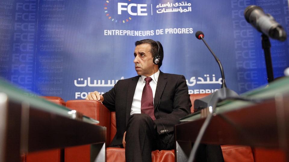 Ali Haddad, dans un fauteuil, avec des écouteurs sur les oreilles.