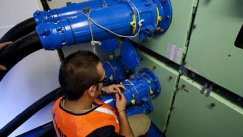 Un homme est devant des tuyaux branchés dans un panneau électrique.