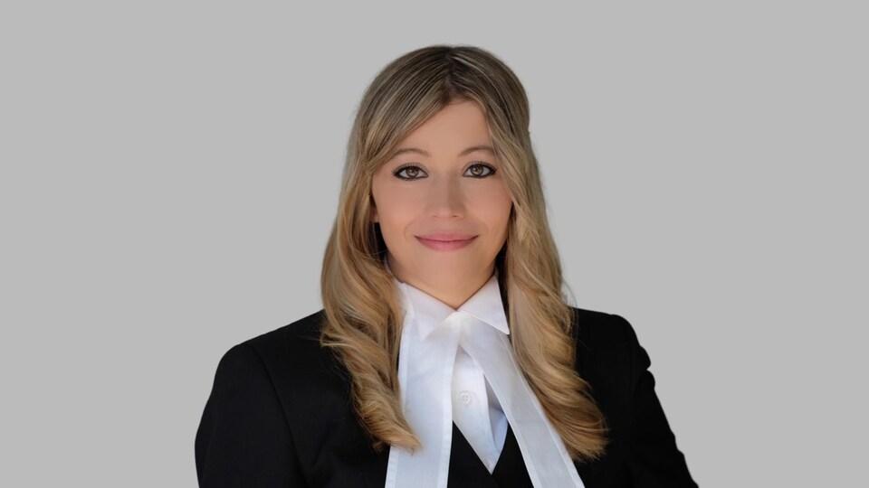 Alina Sklar, vêtue d'une toge d'avocat, pose devant la caméra.