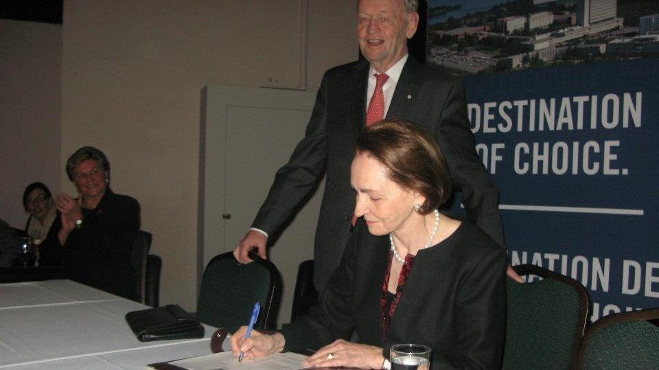 Aline Chrétien qui signe un document