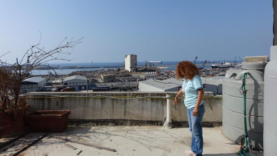Una mujer se encuentra en la terraza frente a las ruinas del puerto de Beirut.