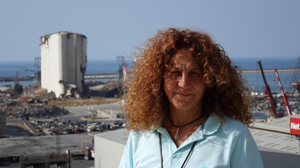 Une femme se tient devant les restes du port de Beyrouth.