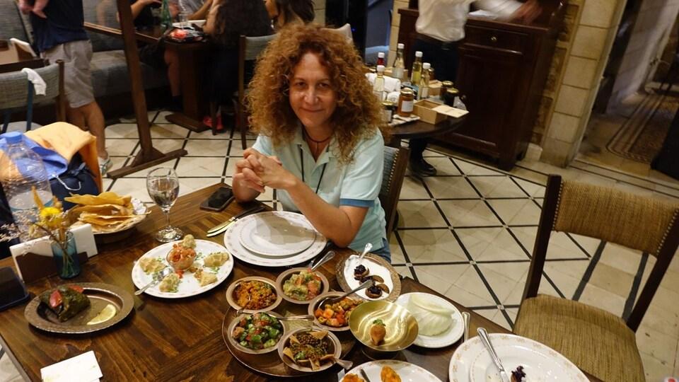 Una mujer se sienta a la mesa de un restaurante frente a varios platos armenios.