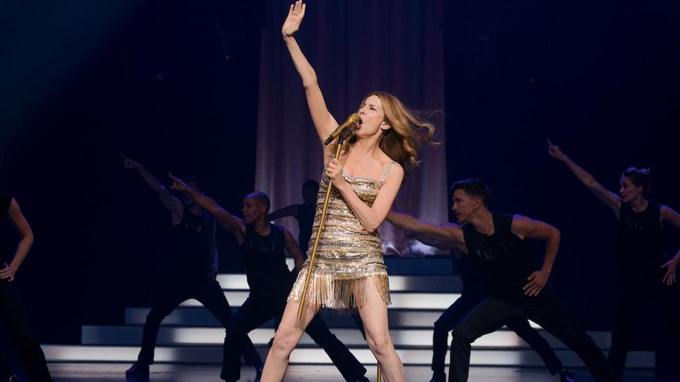 La femme est sur scène avec un micro dans les mains et ressemble beaucoup à Céline Dion.