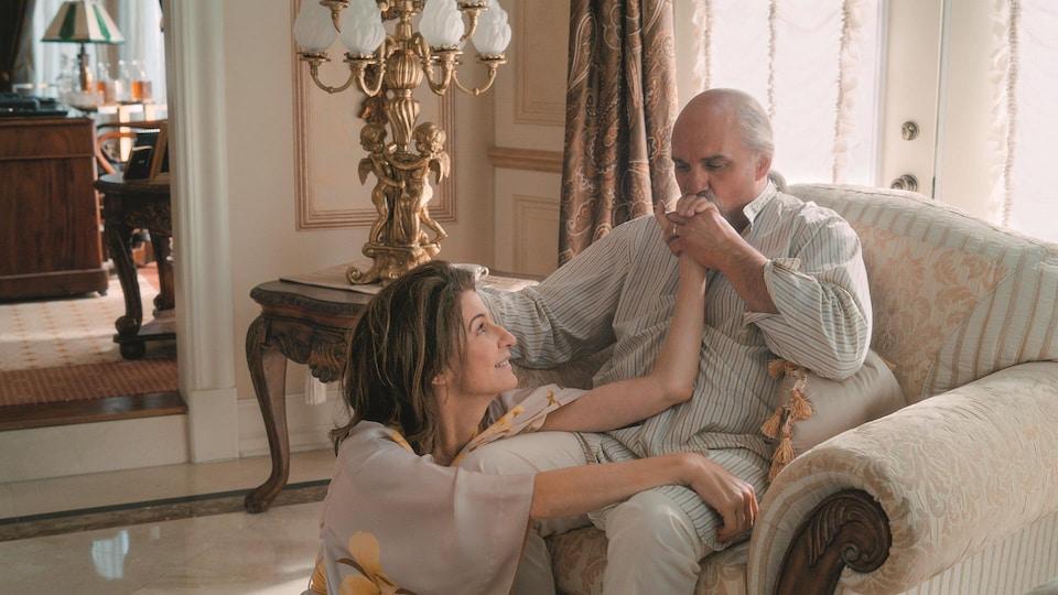 La femme est assise au pied d'un fauteuil dans lequel l'homme est assis. Il lui donne un baiser sur la main.