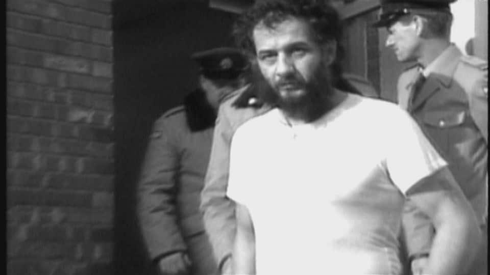 Un homme barbu sort d'un immeuble menotté et entouré de policiers.