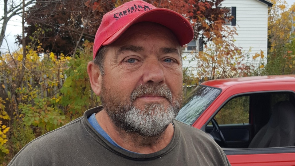 Un homme barbu portant une casquette, à l'extérieur, devant une camionnette.
