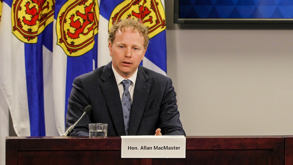 Allan MacMaster assis en conférence de presse.