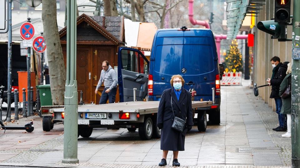 Une vielle femme attend au feu de circulation, devant le marché.