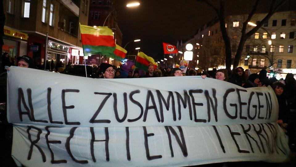 Des manifestants dans une rue de Berlin, le soir. Ils tiennent une banderole sur laquelle est écrit en allemand: Tout le monde ensemble contre le terrorisme d'extrême droite.
