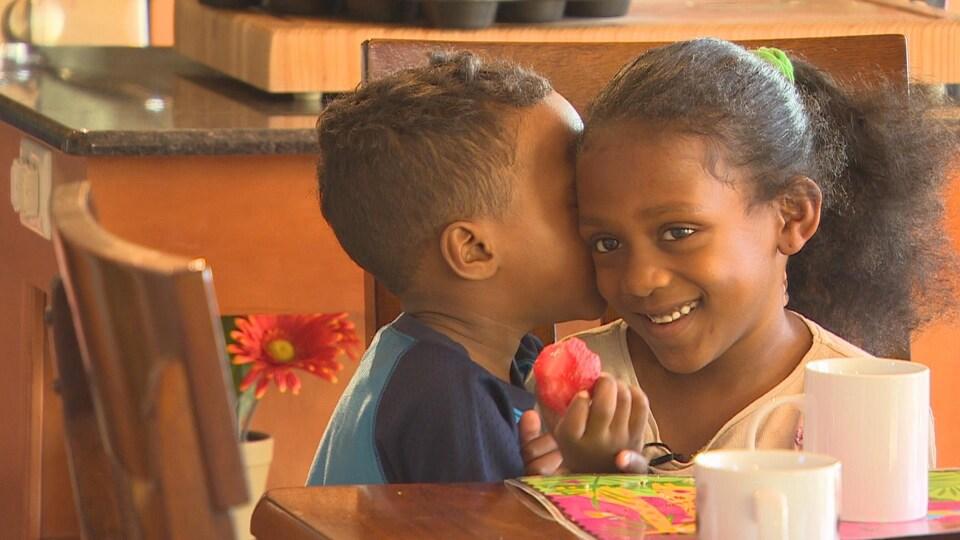 Une fillette sourit, une fraise à la main, pendant qu'un enfant lui murmure quelque chose à l'oreille.