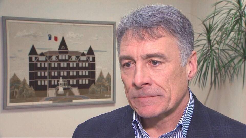 Allister Surette devant un tableau représentant l'Université sur laquelle flotte un drapeau de l'Acadie.
