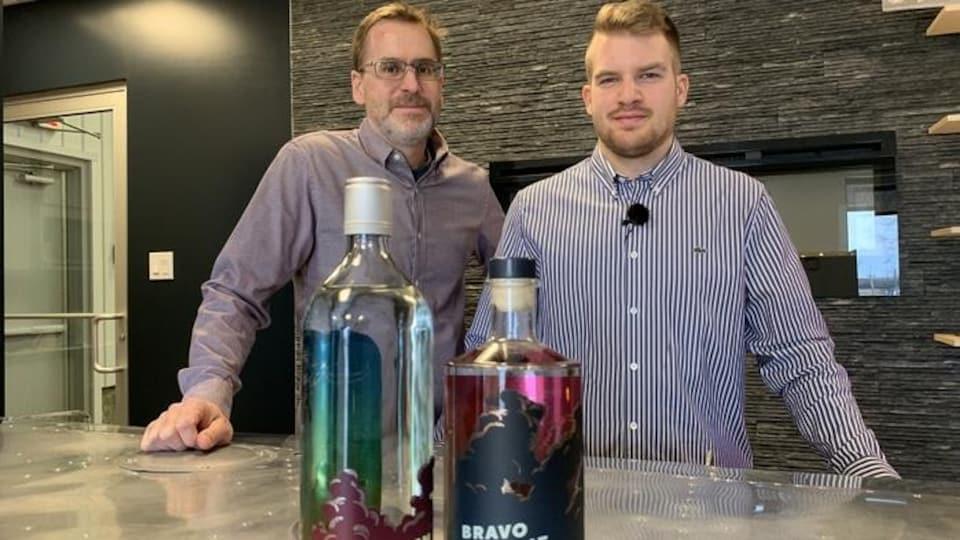 Daniel Corriveau et Alex Gaudreault debout derrière un comptoir où sont déposées deux bouteilles d'alcool.