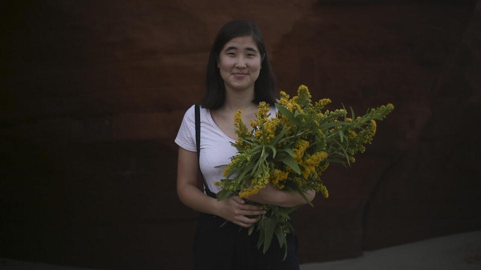Portrait en couleur d'Alphiya Joncas, souriante, en extérieur, sur la plage, avec un rocher rouge en arrière plan. La jeune femme tient une gerbe de fleurs jaunes dans ses bras.
