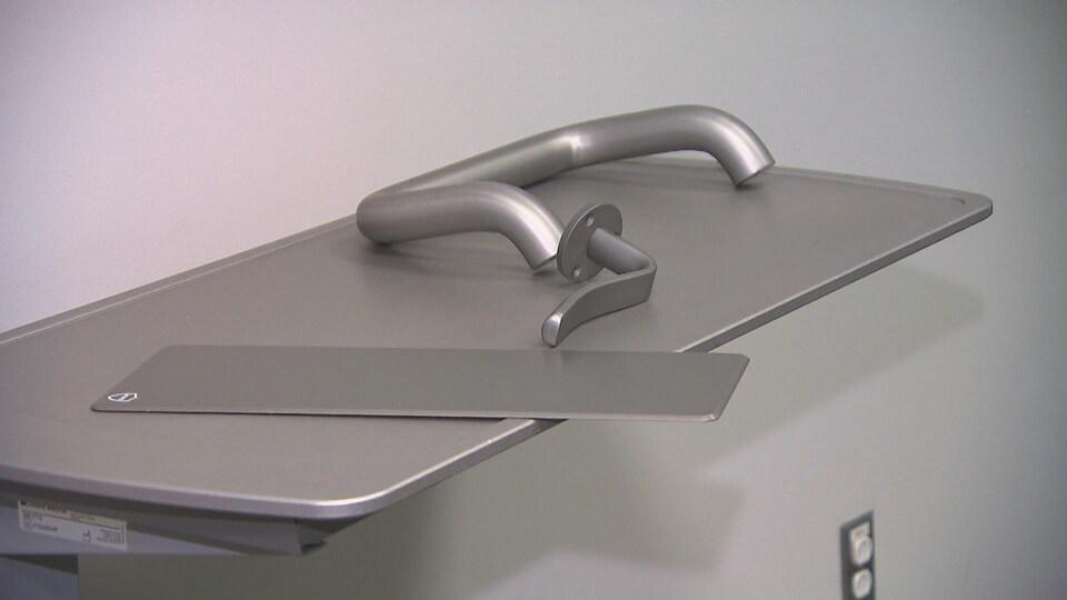 Deux poignées et une plaque d'aluminium placées sur une tablette.