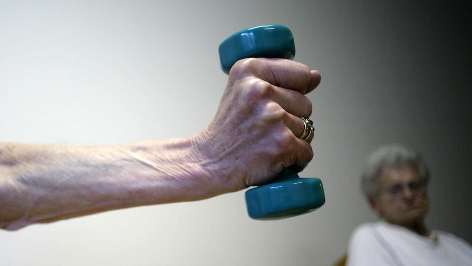 Le bras d'une dame âgée qui tient un petit haltère, avec en arrière-plan une autre dame âgée qui observe.