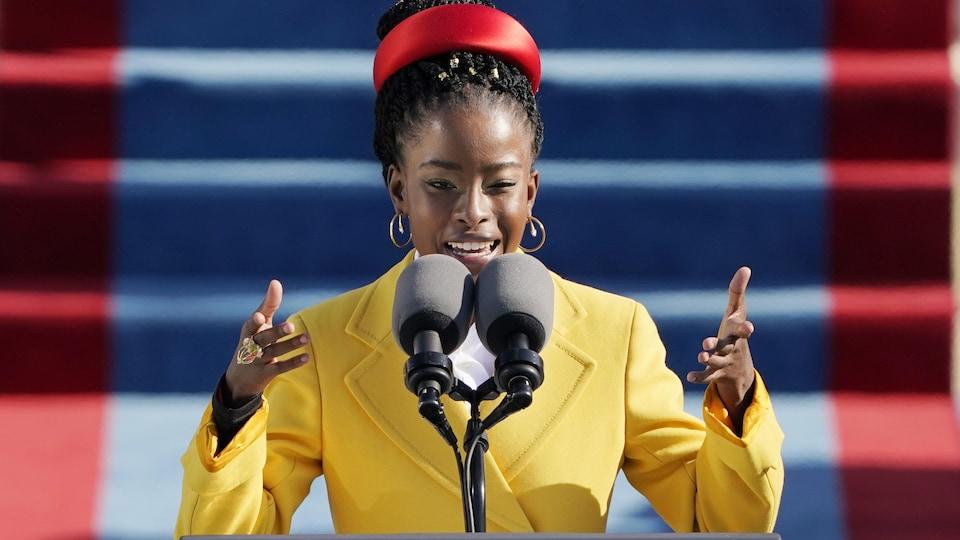 La jeune femme noire porte un veston jaune et un ruban rouge dans les cheveux. Elle est debout derrière deux micros et lève ses mains aux épaules.