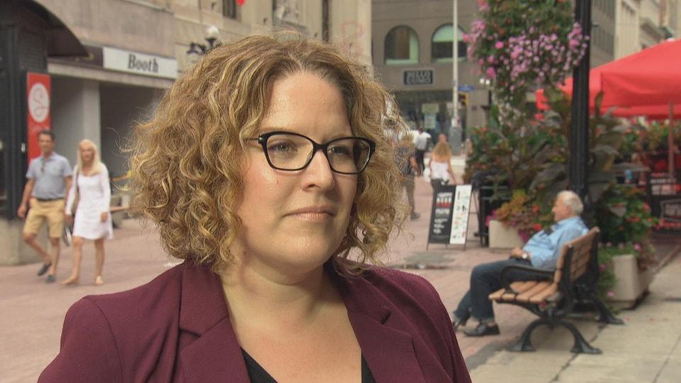 Une femme dans la rue parle en entrevue.