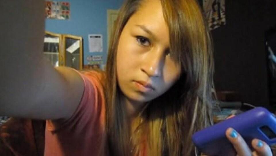 Une jeune femme avec son cellulaire à la main se prend en selfie