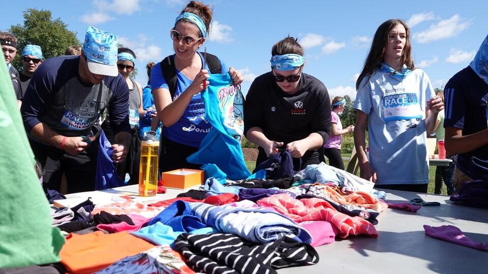 Ciseaux en mains, des gens autour d'une table remplie de vêtements lors d'une épreuve de la course.