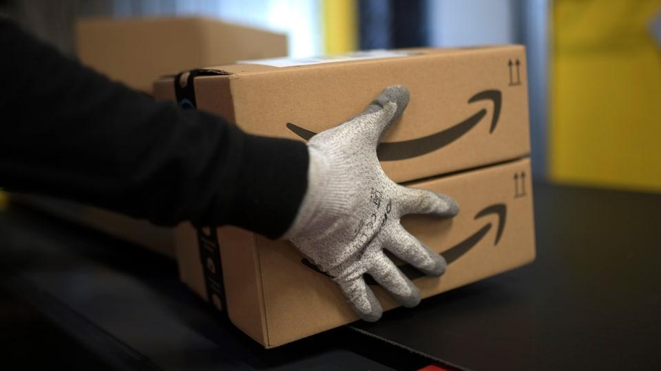 Une personne tient des colis dans un centre de distribution d'Amazon.