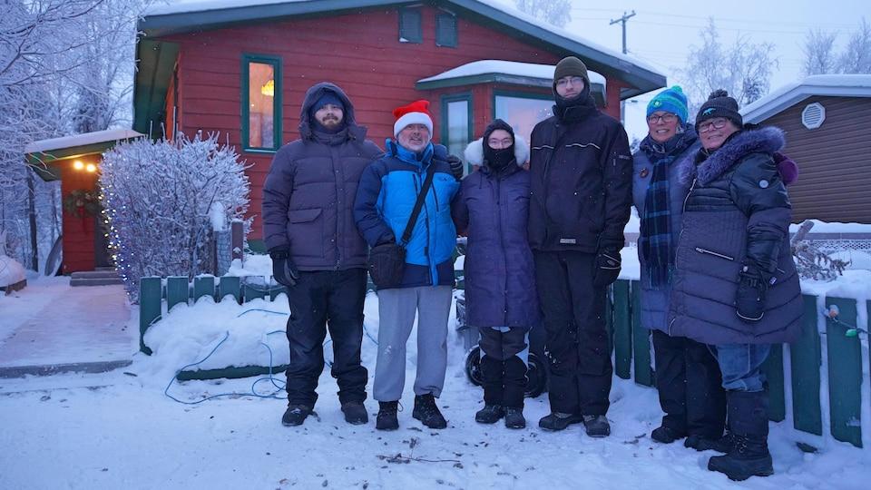 Six personnes habillées chaudement prenant la pose, dehors, devant une maison.