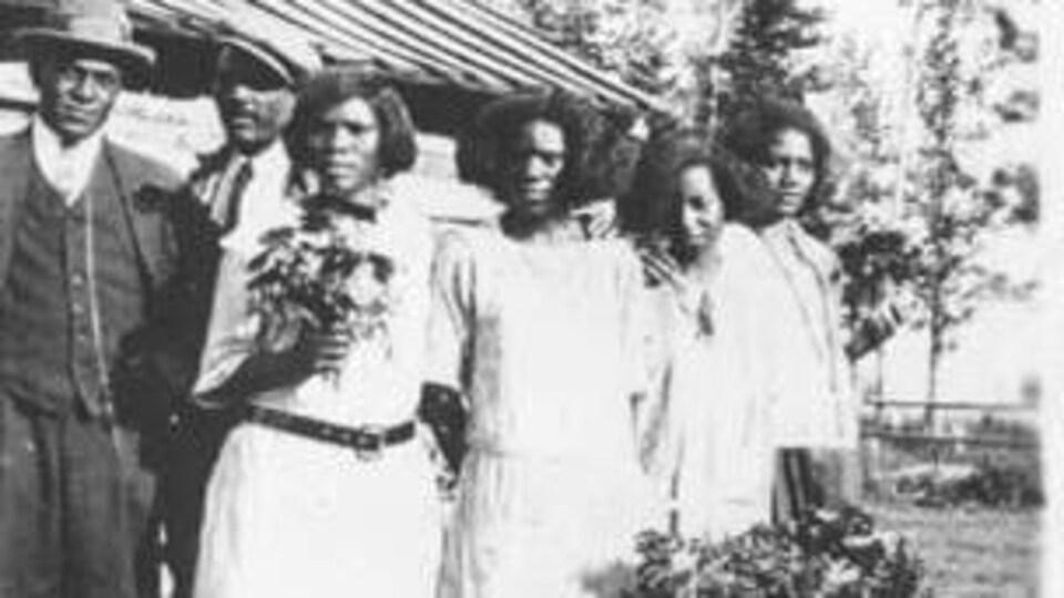 Portrait d'une famille debout à l'extérieur. Une femme porte un bouquet de fleurs.