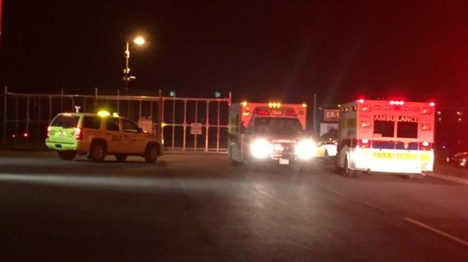 Deux ambulances se trouvent devant l'accès des véhicules d'urgence à l'aéroport d'Ottawa.