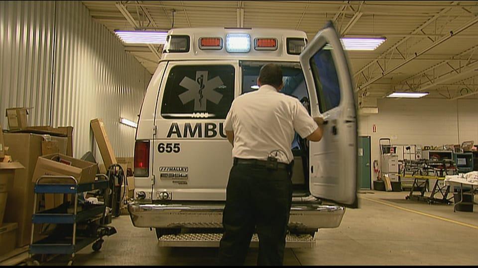 Un travailleur paramédical ouvre la porte d'une ambulance.
