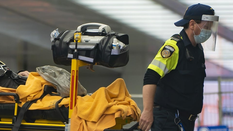 Un ambulancier transporte un patient sur une civière à l'Hôpital Mont Sinaï de Toronto.
