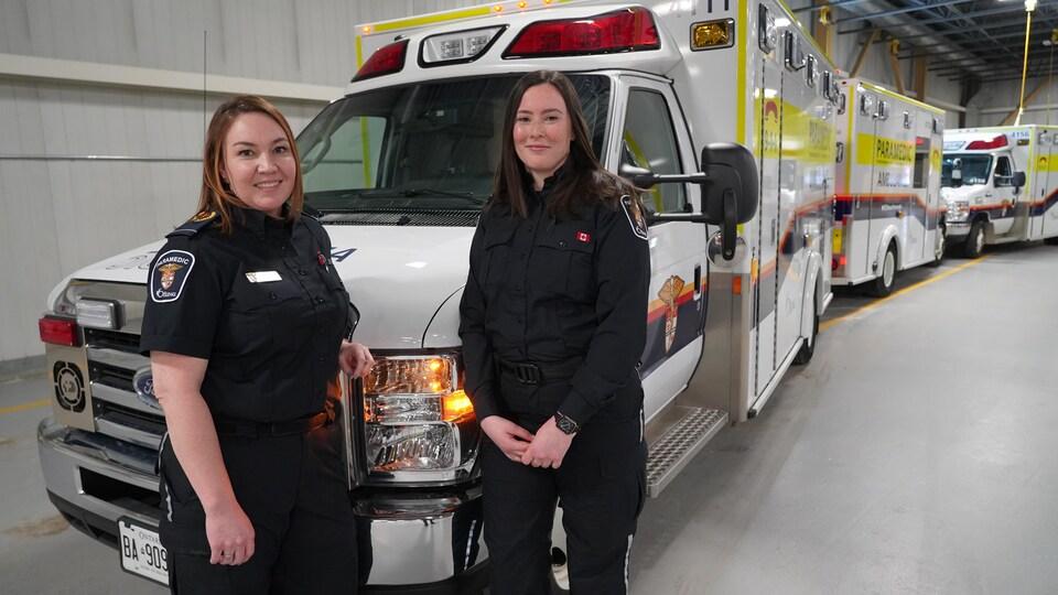 Deux femmes en uniforme devant une ambulance.