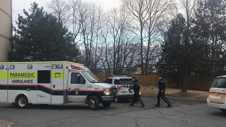Des agents de police munis de lasso de capture, un camion d'ambulanciers paramédicaux et une voiture de police.