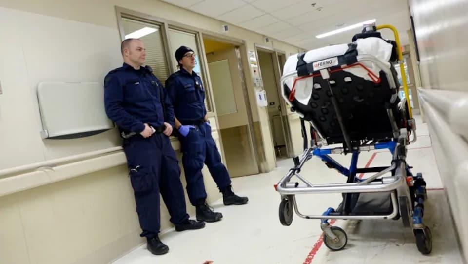 Deux ambulanciers paramédicaux devant une civière.