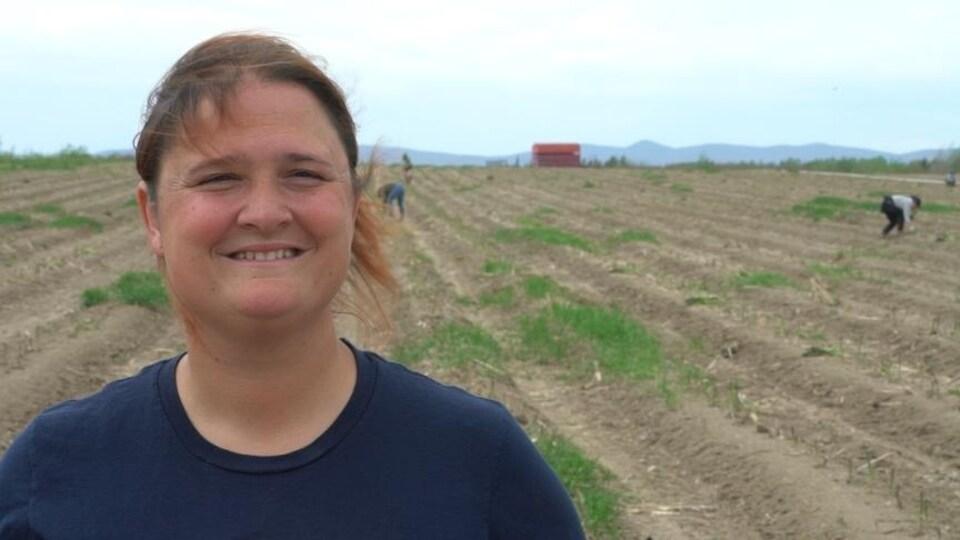 Une femme souriante devant ses champs, avec des cueilleuses en arrière-plan