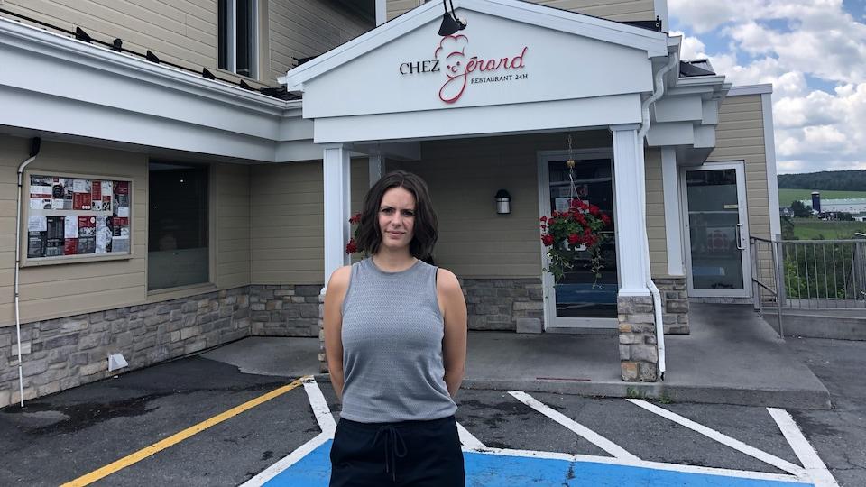 Amélie St-Hilaire devant l'entrée de son restaurant Chez Gérard, c'est le jour, le ciel est nuageux.