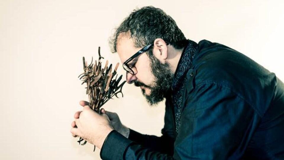 un homme avec un bouquet de plantes dans les mains, pensif, les yeux fermés