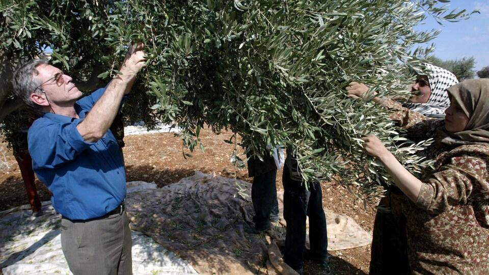 Amos Oz devant un olivier avec deux femmes.