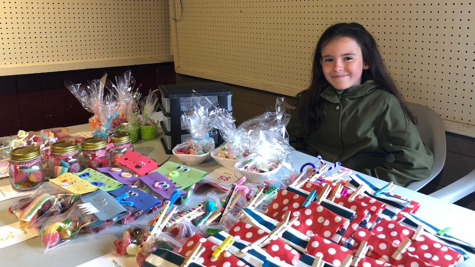 Amy Deschênes sourit. Elle est assise à son kiosque devant ses étalages de bonbons.