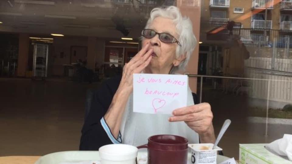 Elle tient un mot sur lequel est écrit : « Je vous aimes (sic) beaucoup », avec un coeur.