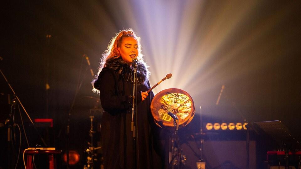 La chanteuse chante sur scène devant un micro et joue du tambour.